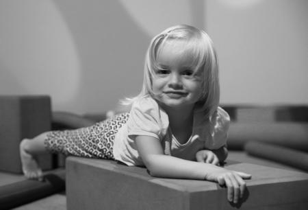 niño modelo: foto en blanco y negro de la niña linda acostado en el piso en la sala de juego. New Plymouth, Nueva Zelanda Foto de archivo