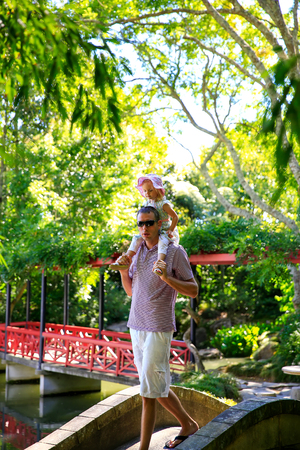 Young tall caucasian man with little daughter on his shoulders.  Chinese Scholars garden in Hamilton Gardens.