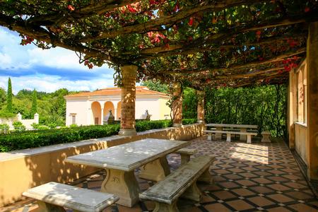 HAMILTON, NZ - FEBRUARY 25, 2015: Italian Renaissance Garden in Hamilton Gardens. Vine covered pergola with marblestone benches and tables.