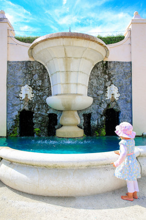 Garden fountain with Angry lion sculptures on the walls in Hamilton Gardens. Cute little girl standing by the fountain