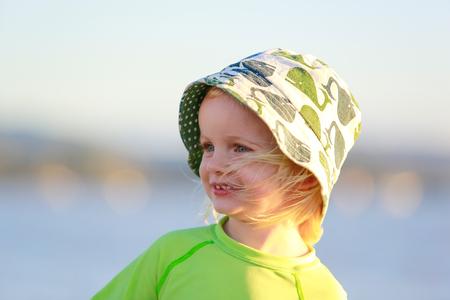sun beach: Adorable child in yellow shirt on the beach. Coromandel, New Zealand Stock Photo