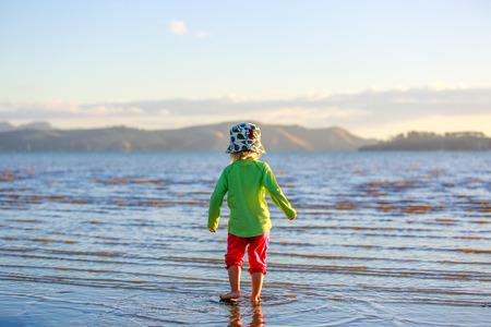Cute Little girl walking on Coromandel beach, New Zealand.