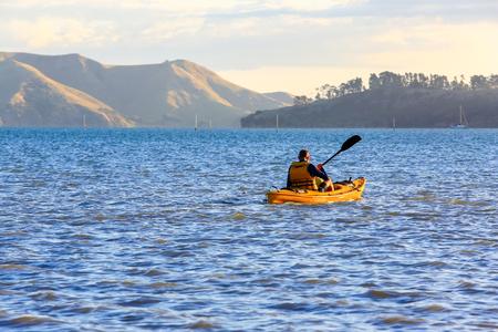 Man kayaking in Coromandel, New Zealand.