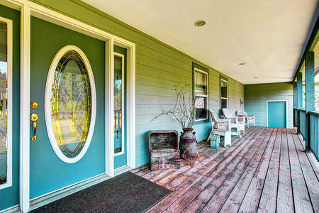 white trim: Large covered porch with white chairs and turquoise front door. Northwest, USA Stock Photo