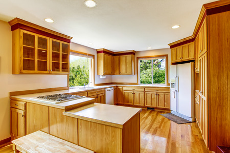 Light brown kitchen cabinets, white appliances and hardwood floor. Country house interior. Northwest, USA Stock Photo