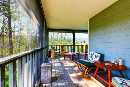 Long covered porch in turquoise color with comfortable chairs. Northwest, USA