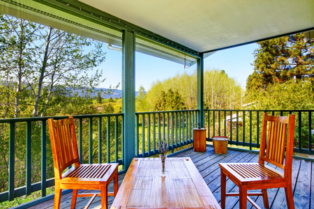Covered porch with wooden table setting and nice forest landscape.  Northwest, USA