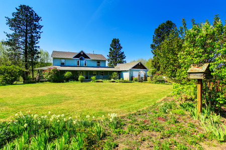 curb appeal: Beautiful curb appeal of large blue  country house. Well kept lawn with flower beds. Northwest, USA