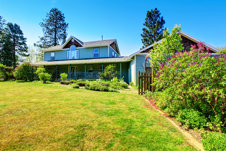 Beautiful curb appeal of large blue  country house. Well kept lawn with flower beds. Northwest, USA