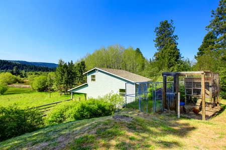 Blue country house backyard view with two metal cages. Northwest, USA