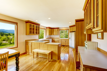 cabinets: Light brown kitchen cabinets, white appliances and hardwood floor. Country house interior. Northwest, USA Stock Photo