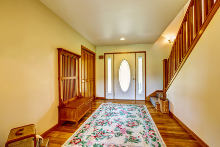 Hallway interior of country house with white  front door and colorful rug. Northwest, USA