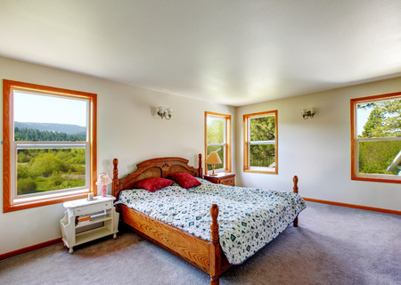 White bedroom interior with wooden carved bed and carpet floor. Northwest, USA