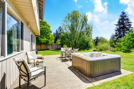 lawn area: Backyard concrete floor patio area with hot tub. Well kept lawn around. Northwest, USA