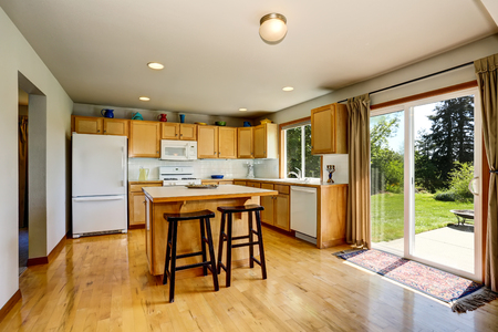 Kitchen room interior with light brown cabinets and island and door to backyard. Northwest, USA