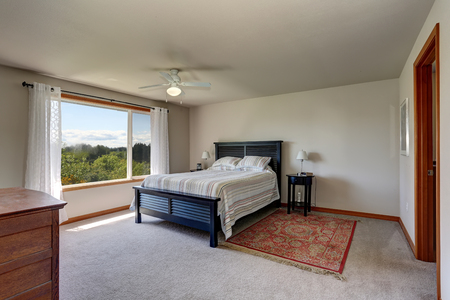 Bedroom interior with beige walls, rug and white curtains. Northwest, USA