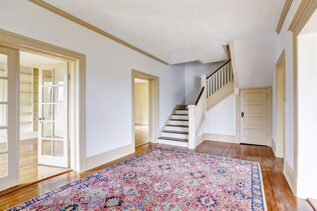 Hallway interior in white tones with hardwood floor and rug. View of stairs. Northwest, USA Stock Photo