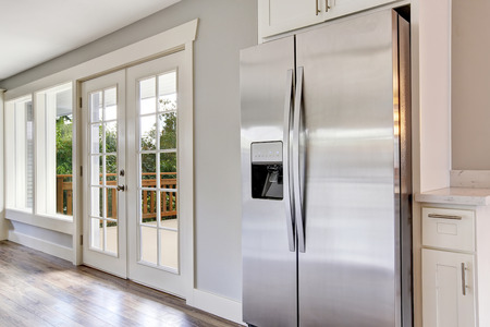refrigerator: Bright kitchen room with steel appliances and granite tops. Northwest, USA