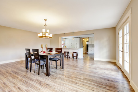 Open floor plan spacious room interior. Dining area with dark brown wooden table set. Northwest, USA Stock Photo