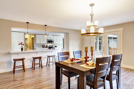 areas: Open floor plan spacious room interior. Dining area with dark brown wooden table set. Northwest, USA Stock Photo
