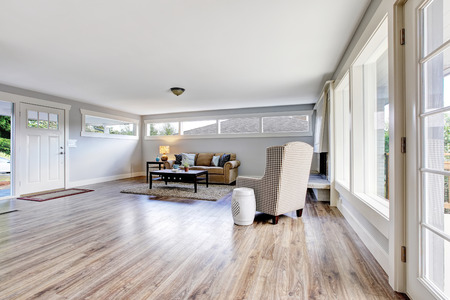 floor rug: Spacious living room interior with polished hardwood floor, rug and dark brown coffee table. Northwest, USA