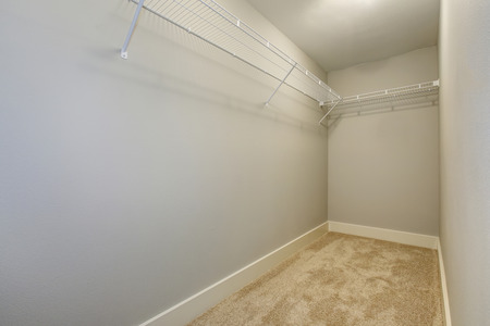 Empty narrow walk-in closet with shelves and carpet floor. Northwest, USA