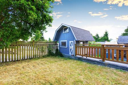 小さな青い納屋小屋、木製の柵が付いている裏庭の家庭菜園。米国北西部