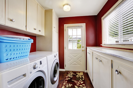 laundry room: Laundry room interior with white cabinets and red walls. Northwest, USA Stock Photo