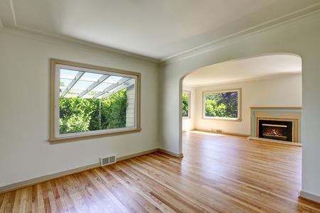 open floor plan: Open floor plan empty living room interior with polished hardwood floor and fireplace. Northwest, USA