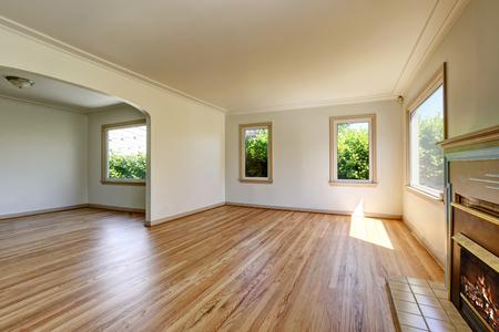 Open floor plan empty living room interior with polished hardwood floor and fireplace. Northwest, USA
