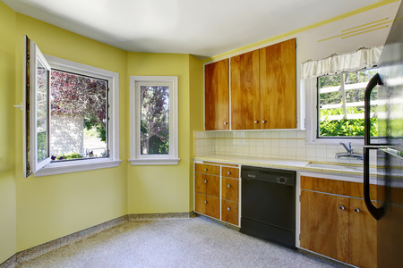 yellow walls: Small kitchen room interior with yellow walls, wooden cabinets and tile counter top. Northwest, USA Stock Photo