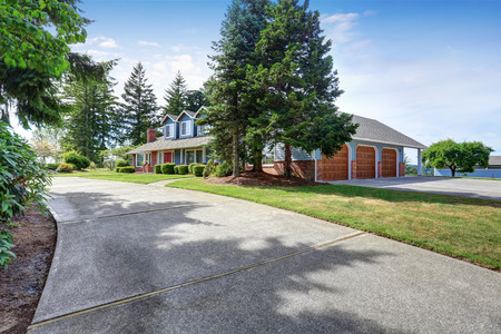 white trim: American house exterior with blue and white trim, three garages. Also red front door, well kept garden and driveway. Northwest, USA Stock Photo