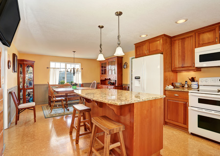 counter top: Kitchen room interior with island, wooden cabinets and granite counter top. Northwest, USA