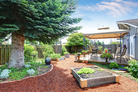 Small garden beds at the backyard. Walkout deck with patio area at the background. Northwest, USA Stock Photo