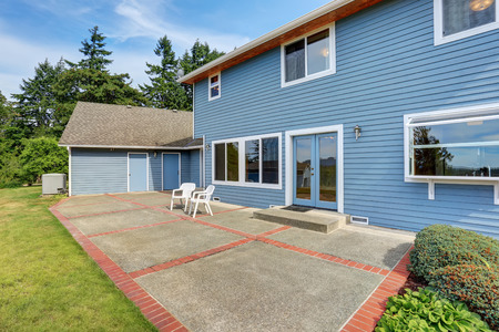 Blue house backyard with concrete floor patio area and well kept garden. Northwest, USA