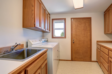 cabinets: Laundry room with wooden cabinets and stainless sink. Northwest, USA