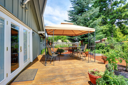 Backyard patio area with table set and opened orange umbrella. Northwest, USA