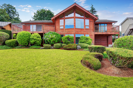 home exterior: Luxury house exterior with wooden panel trim, garage and well kept garden around. Northwest, USA Stock Photo
