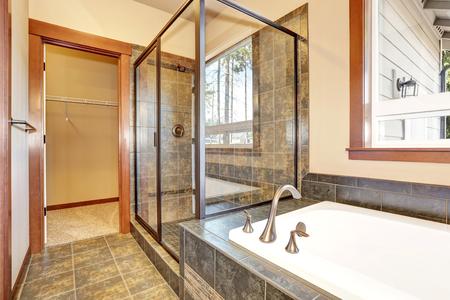 cabine de douche: intérieur de salle de bains avec garniture de carreaux de marbre. Vue de la cabine de douche en verre et baignoire blanc baignoire. Northwest, États-Unis