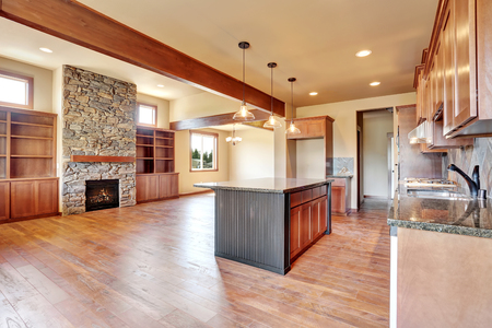 Open floor plan. Kitchen room interior with wooden cabinets, island and granite counter top. Connected to living room with stone fireplace. Northwest, USA Stock Photo