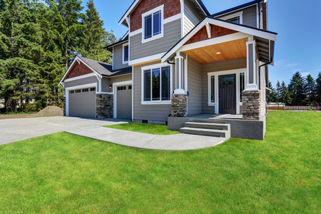 Classic large craftsman American house exterior with rocks trim, garage and concrete floor porch. Also well kept lawn around. Northwest, USA.