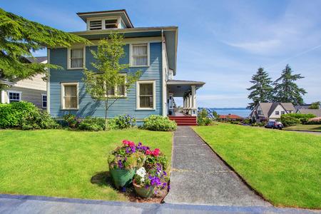 Clásico gran artesano exterior de la casa americana vieja en tonos azules con cuidado jardín y vista perfecta del agua. Noroeste, EE.UU..