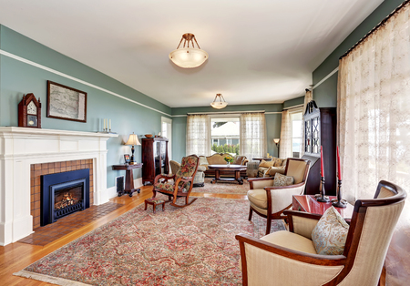 traditional living room: Traditional living room interior in blue and white tones, fireplace and rug. Northwest, USA