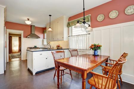 silla de madera: Interior del sitio de la cocina clásica con muebles blancos, encimera de granito y piso de madera. También paredes rojas. Noroeste, EE.UU.