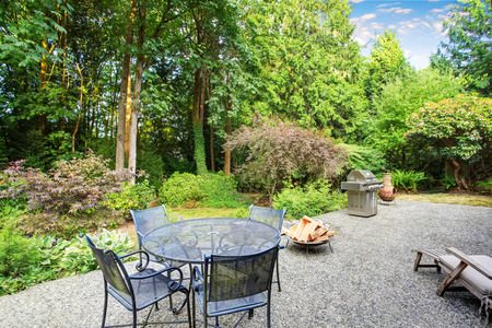 Vintage back patio with clay fire pit, furniture, and lots of greenery. Northwest, USA