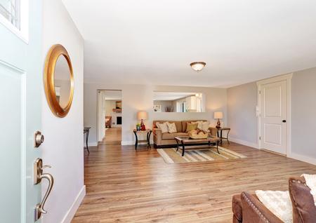 open floor plan: Open floor plan living room interior in white tones with hardwood floor. Open door view. Northwest, USA Stock Photo