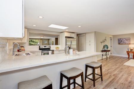white kitchen: Modern kitchen room interior in white tones with hardwood floor. Open floor plan. Northwest, USA