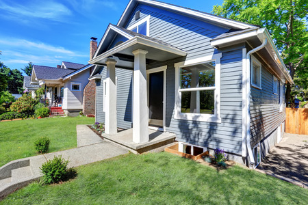 American house exterior with blue siding trim and small concrete floor porch with columns. Northwest, USA Stock Photo