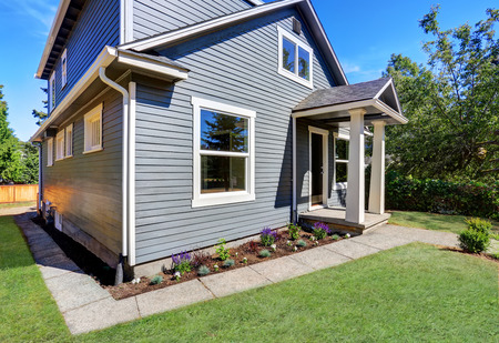 american house: American house exterior with blue siding trim and small concrete floor porch with columns. Northwest, USA Stock Photo