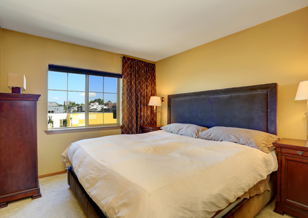 king size bed: Bedroom interior with king size bed and brown curtains. Northwest, USA Stock Photo
